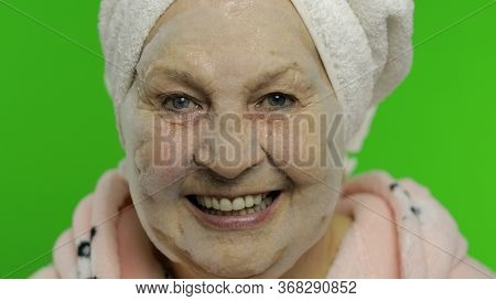 Adult Senior Caucasian Woman Grandmother In Bathrobe And Towel Over Head Applying Cosmetic Bubble Fa