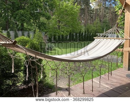 Empty Hammock To Relax On The Terrace Of The House. A Hammock Hangs In The Yard In A Green Garden. C