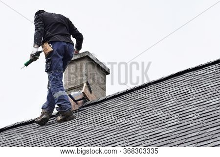 Roofer Construction Worker Repairing Chimney On Grey Slate Shingles Roof Of Domestic House, Sky Back