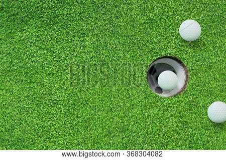 Top View One Of White Golf Balls In Hole On Green Grass Meadow Field.