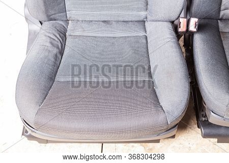 Close-up Of A Car Seat Chair Made Of Gray Fabric With A Checkered Pattern Before Cleaning In A Auto
