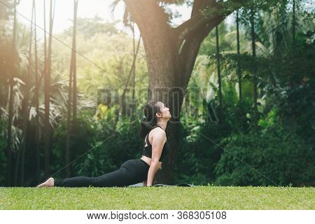 Asian Woman Practicing Yoga In Cobra Pose (bhujangasana) On The Mat In Outdoor Park.