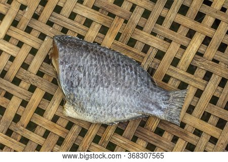 Thai Food Preservation. Preservation Tilapia Nile Fish By Cutting Head.salted And Dried In Sunligh.