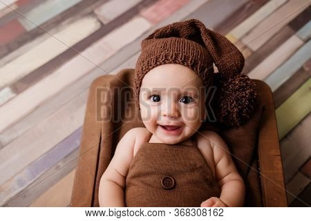 Cute Newborn Baby. Smiling Baby On A Dark Background. Closeup Portrait Of Newborn Baby. Baby Goods P