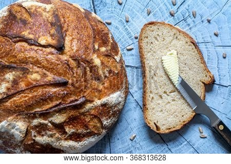 Top View Of  Artisan Bread Loaf And A Slice With Butter Surrounding By Some Sunflower Seeds On Woode