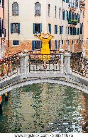 Woman In Yellow Sundress Standing On The Bridge Cross Venice Canal