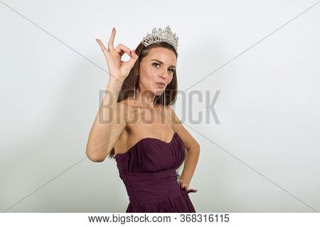 Young Attractive Woman Brunette In Purple Stylish Dress, With Crown On Head On White Background, Hap