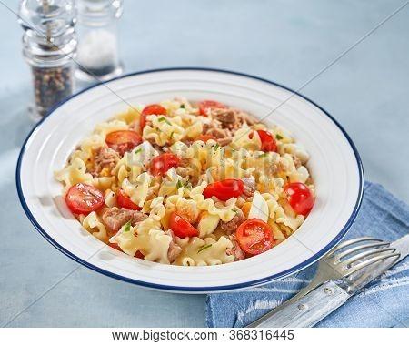 Healthy Fusilli Or Rotini Pasta Salad With Tuna, Vine Tomatoes And Mozzarella Cheese On A Light Back