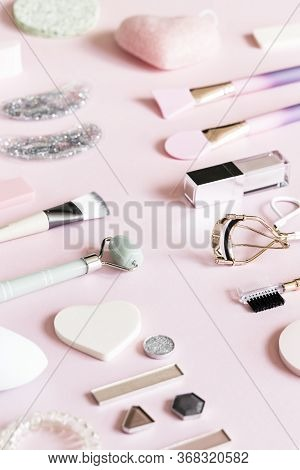 Cosmetic Products: Lip Gloss, Lipstick, Jade Roller, Brushes, Patches And Eyelash Curler On Pink Bac