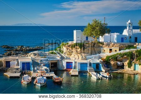 Typical Greece scenic island view - small harbor with fishing boats in crystal clear turquoise water, traditional white houses church. Mandrakia village, Milos island, Greece.
