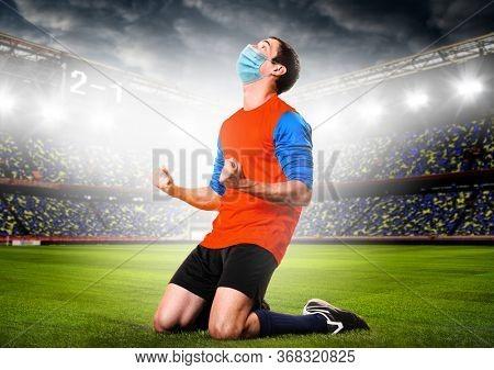 Soccer or football player wearing mask. Team sports player in medical mask emotionnally kneeling on stadium during coronavirus outbreak.