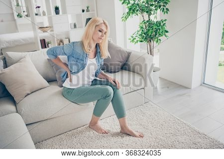 Profile Photo Of Unwell Displeased Blond Mature Lady Sit Couch Stay Home Quarantine Hold Hand On Spi