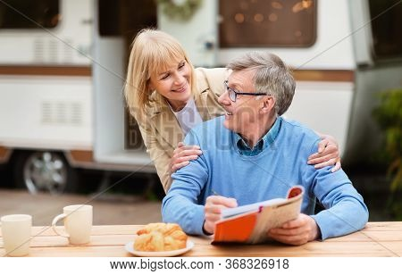Senior Woman Hugging Her Husband While He Solving Crossword During Breakfast At Campsite
