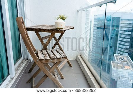 Wooden Table And Chair On The Balcony Overlooking The Modern Big City. Cozy Balcony