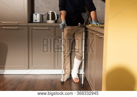Cropped View Of Man With Broken Leg Holding Crutch And Cleaning Kitchen Worktop
