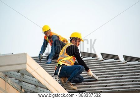 Roof Repair,construction Worker Using Nail Gun To Install New Roof On Top Roof,residential Building
