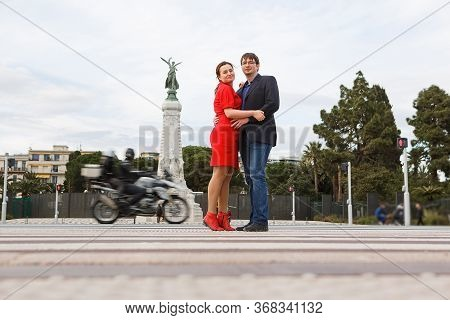 Couple Cross The Road In Nice. Glorious Monument Symbolizes Freedom And Well-being Of City. South Of