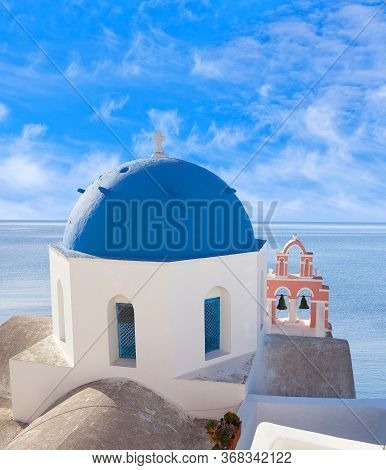 Blue Domed Anastasi Greek Church And Belfry Against Volcano Caldera In Oia Town On Santorini Island,
