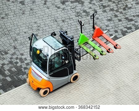 Green And Red Pallet Truck Loaded On A Small Forklift
