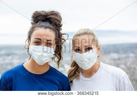 Two diverse women wearing personal protective equipment masks as they walk outdoors. Wearing essential face masks during COVID-19 pandemic in an outdoor setting