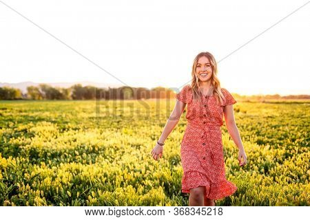 Portrait of a smiling Happy girl walking among the wild flowers in a large field on a summer evening.