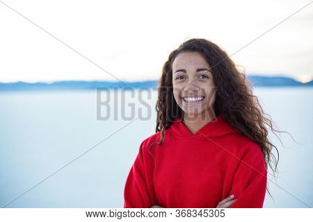 Outdoor portrait of a beautiful mixed race teenage girl. Cute diverse head and shoulders photo of a real teen girl outdoors