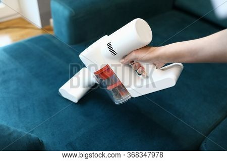 Close-up Of Womans Hand Cleaning Green Sofa With Small White Compact Vacuum Cleaner. Renovation And