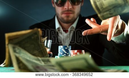 Poker player throwing US dollars banknotes. Concept of hazard gaming, poker chips on table