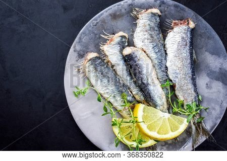 Fried sardines with lemon slices and herbs offered as closeup on a modern design plate with copy space left