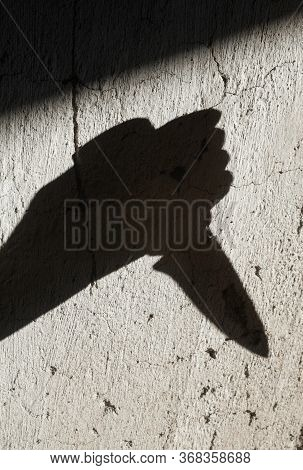 Shadow Of The Hand Holding A Big Sharp Knife. Murderer, Killer Or Robber With A Knife. Criminal. Cri