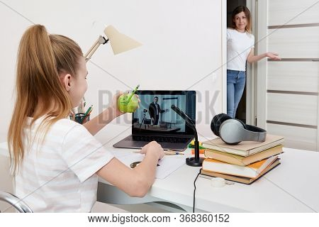 Mother Watching Her Daughter Doing Homework On Laptop At Home