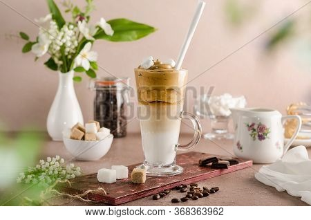 Cold Coffee Dalgon In A Tall Glass On A Beige Wooden Background With Marshmallows And A Straw. Foam
