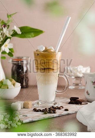 Cold Coffee Dalgon In A Tall Glass On A Beige Wooden Background. Foam Whipped With A Mixer Made Of S