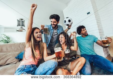 Very Excited Friends Having Fun By Watching Football Match And Eating At Home, Indoors. Friendship,