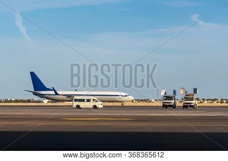 International Airlines Plane Parking Outside A Terminal In Airport. White Passenger Airplane, Side V