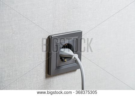 A Gray Outlet On The Wall Which Includes A Device With A White Cord. Charging From A Power Outlet