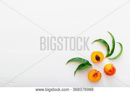 Peaches With Leaves On White Wooden Background With Peach In Halves. Flat Lay Copy Space Composition