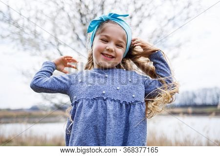 Adorable Little Girl Playing In Blooming Apple Tree Garden On Easter Egg Hunt, Runing And Smiling. C