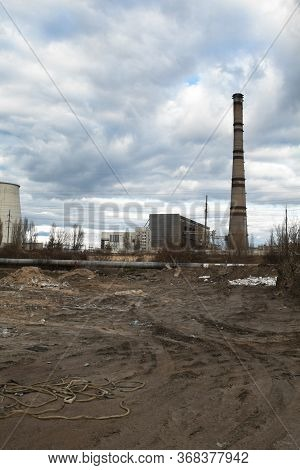 Garbage Dump And Industrial Plant In The Background. Environmental Pollution. Wheel Ruts On The Grou