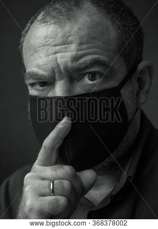 A man in a medical mask with a finger at his mouth. Coronavirus fake news and conspiracy theories concept