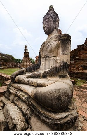 A Stone Image Of Buddha Sitting Amongst The Ruins Of Wat Maha That. In The Ancient City Of Ayuthaya,