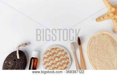 Bamboo Toothbrushes, Face And Body Sponges, Essential Oil And Pumice On White Background. Copy Space