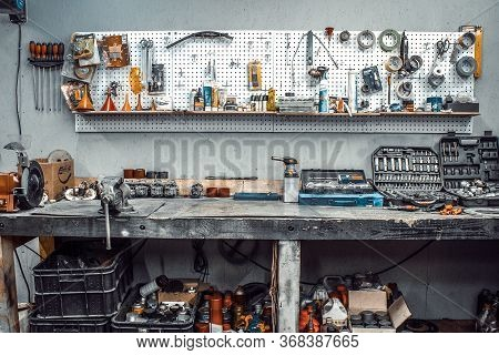 Moto Workshop With Hand Tools. Workbench With Sets Of Keys, Screwdrivers, Ploskobets, Electrical Tap