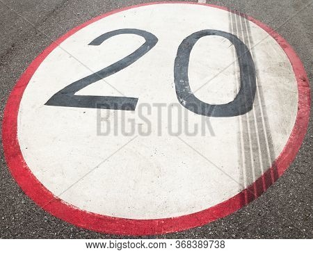 Speed Limit Sign (20 Kilometers/miles Per Hour) Painted On The Asphalt Surface.