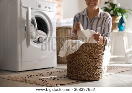 Young Woman With Laundry Basket Near Washing Machine At Home