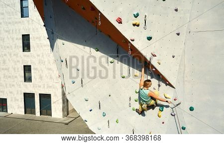Active Sporty Woman Practicing Rock Climbing On Artificial Rock Wall In Climbing Gym. Reaching Holds