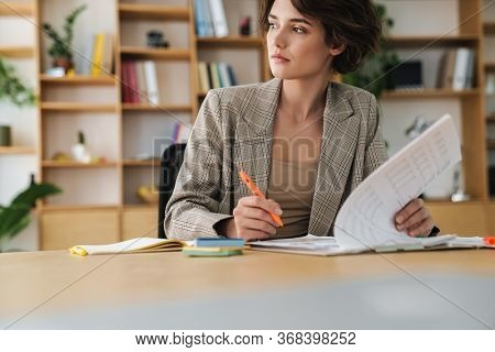 Beautiful concentrated young businesswoman sitting at the office desk, looking through documents