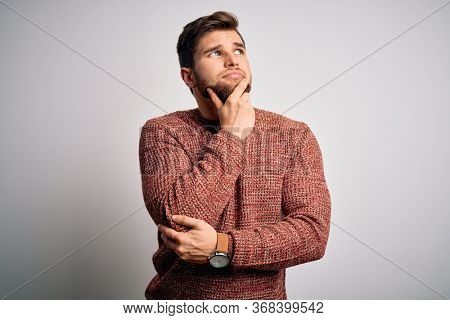 Young blond man with beard and blue eyes wearing casual sweater over white background with hand on chin thinking about question, pensive expression. Smiling with thoughtful face. Doubt concept.