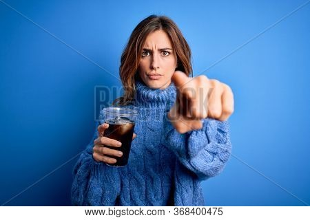 Young beautiful brunette woman drinking glass with cola refreshment over blue background pointing with finger to the camera and to you, hand sign, positive and confident gesture from the front