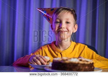 Happy messy child after party. He ate a celebration cake. Cute boy with a dirty face from sweet cake. Happy boy with cone on head celebrates his birthday. Caucasian child and birthday cake